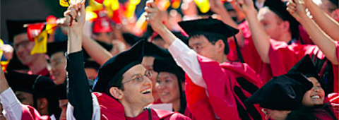 PhD students waving flags at Commencement