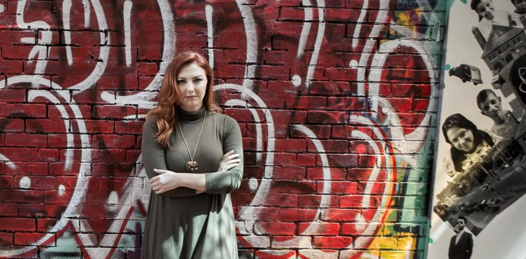 Samantha Hawkins stands against a wall filled with graffiti