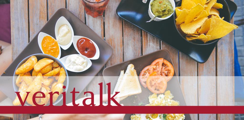 Veritalk logo over an image of a hand reaching for food on a wooden table - including bread, fries, dips, and a drink