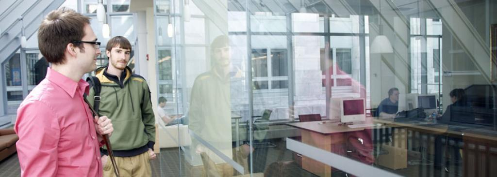 Two students looking through glass door of office