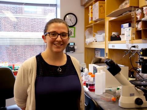 Maddy Mcfarland, wearing a blue shirt and tan sweater, smiles in front of lab equipment