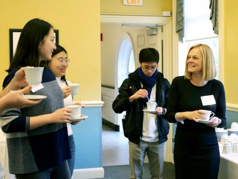 Four students surround Dean Emma Dench, all hold teacups