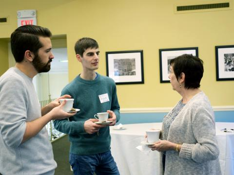 Two students hold tea cups and talk with Leslie Kress, from the Office of the Dean