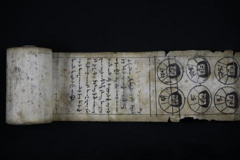 Partially unrolled scroll with handwritten text and illustrations.
