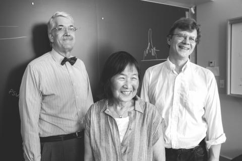 John Doyle (in a button down and bow tie), Evelyn Hu (smiling and wearing a button down shirt), and Mikhail Lukin (also smiling and wearing a button down shirt), stand in front of a blackboard with a roughly drawn chalk graph