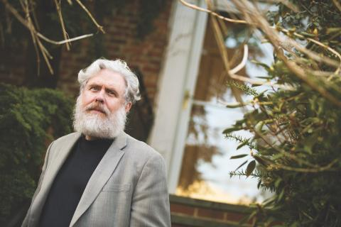 George Church, with a white beard and wearing a blazer, stands outside