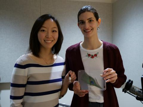 Victoria Hwang (L) holds a vial of lab-made structural color, Annie Stephenson (R) holds a peacock feather.