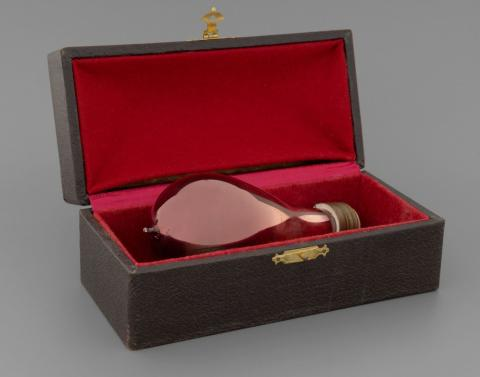 A lightbulb made of red glass is displayed in a wood and red velvet box