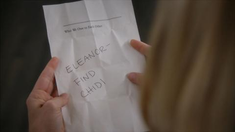 "Hand holds a torn page from the book ""What We Owe to Each Other"" with the words ""Eleanor Find Chidi"" scrawled on it"