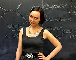 Sabrina Gonzalez Pasterski standing in front of a chalkboard with physics equations on it
