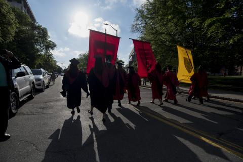 Graduates are silhouetted against a sunny background