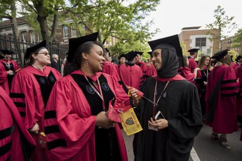 Two students in Commencement robes smile at each other