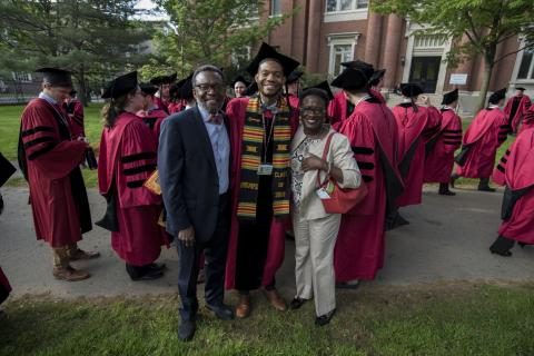 Man in academic regalia stands in between two smiling people