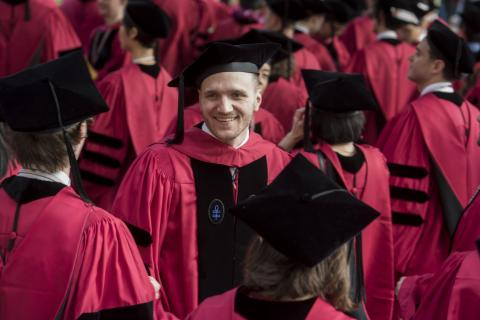 Smiling man stands surrounded by people in red academic robes