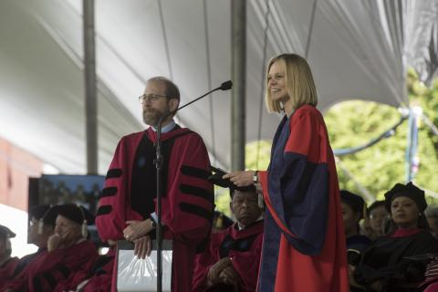 Emma Dench, in academic regalia, stands in front of a microphone
