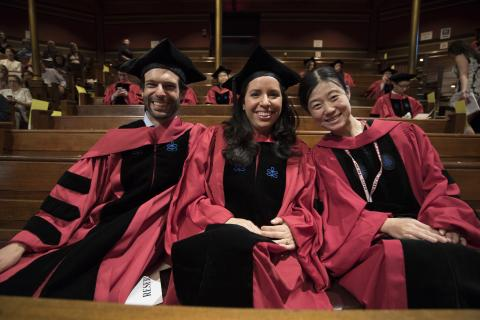 Three students sit in academic robes in Sanders Theatre benches