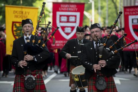 two men with bagpipes and one with a drum lead a parade