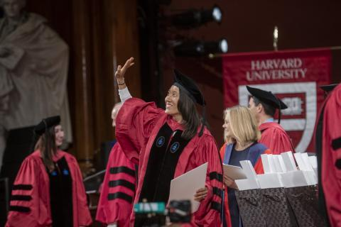 Smiling woman stands in academic regalia and waves from the stage