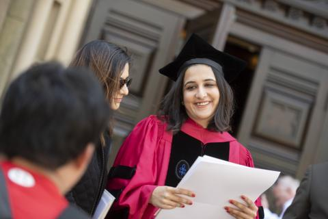 Smiling woman holds her diploma