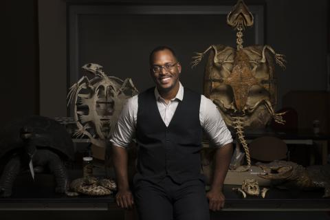 Shane Campbell-Staton poses in front of two animal skeletons