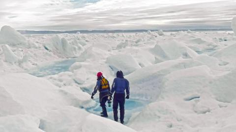 Two people walk across an icy landscape