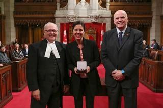 Melanie Adrian holding her medal from the Canadian Senate, with Speaker of the Senate George Furey to her left and Senator Vernon White to her right.
