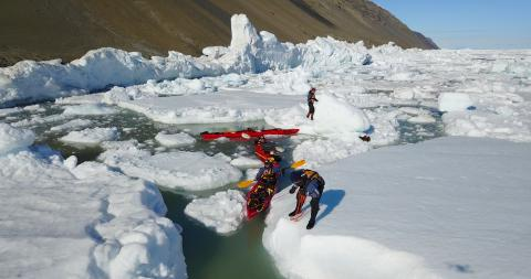 A group of people tries to navigate red kayaks through ice and water.