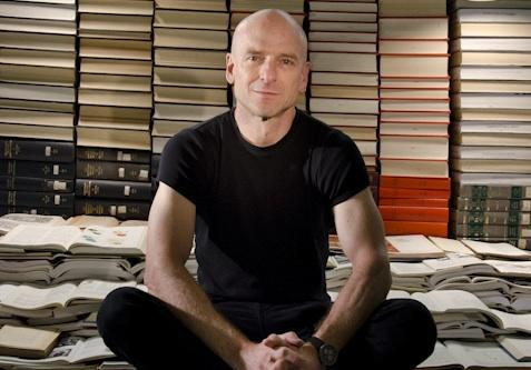 Jeffrey Schnapp sits in a pile of books