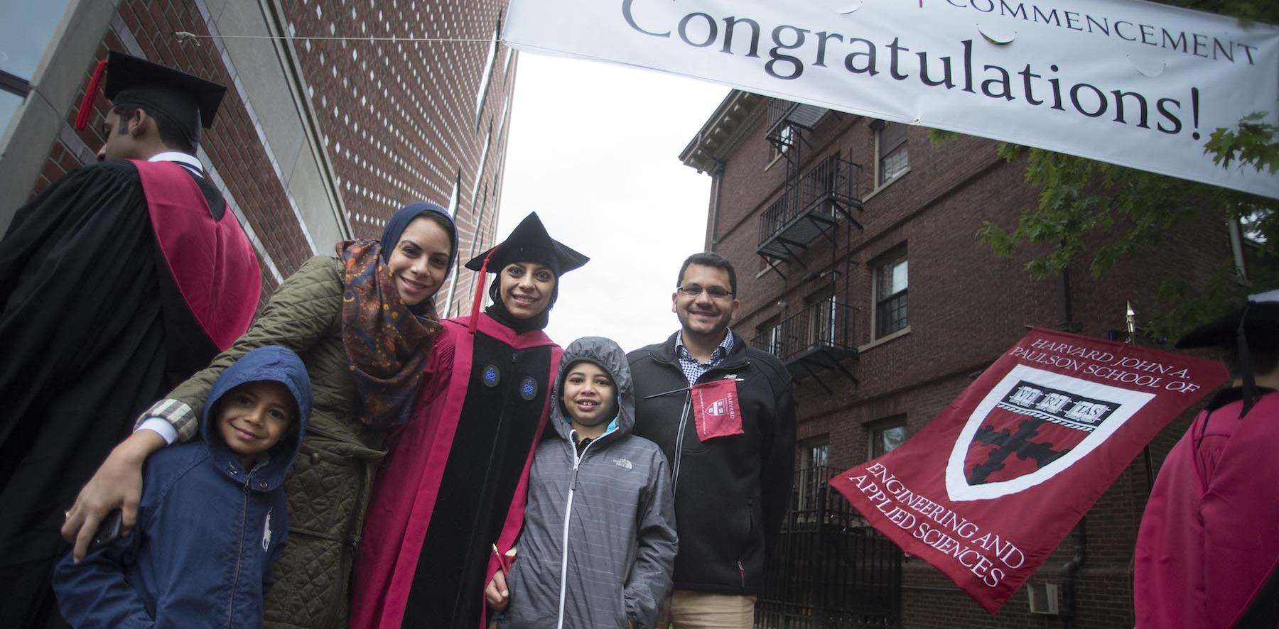 "A family of 5 stands under a ""Congratulations"" banner."