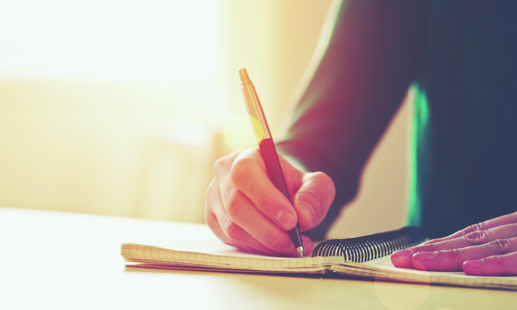 Hand writing in a notebook with a pen