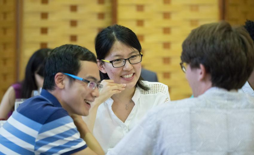Three students sitting around a dining table smiling