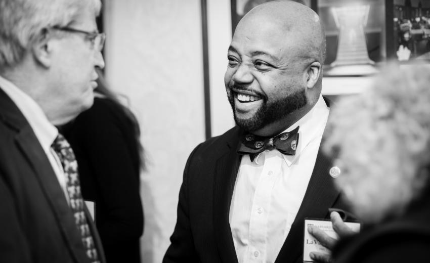 Alum in a bowtie smiling at an event