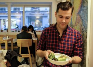 Person wearing plaid shirt looks down at a bowl of food in a restaurant
