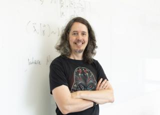 Jameson Quinn, in a black Star Wars t-shirt, leans against a white board