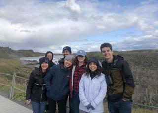 A cluster of 7 students in parkas pose, smiling, in front of a blue sky and rocky landscape