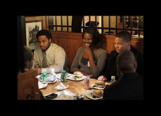 Female and male Morehouse College students seated and enjoying conversation at a cafe during a visit to Harvard.