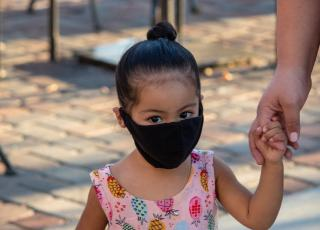 Young child wearing a mask, holding adult's hand