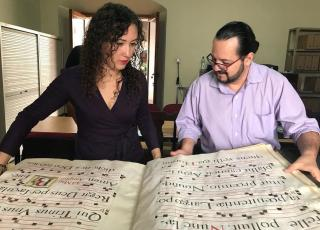 Two people opening an oversize book with very old musical notation inside.