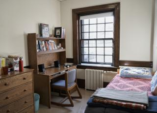 Small, occupied room in Perkins Hall with desk, chair, bed