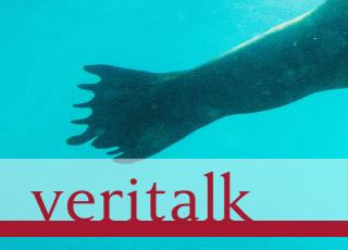 "A human-like tail of a seal floats in murky blue-green water. The word ""Veritalk"" appears in crimson."