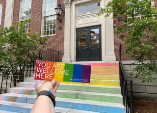 You Belong Here sticker being held in front of chalk-colored steps of the GSAS Student Center