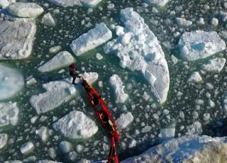A team pulls red kayaks over ice and water