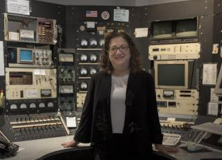 Sara Schechner poses next to the cyclotron control console