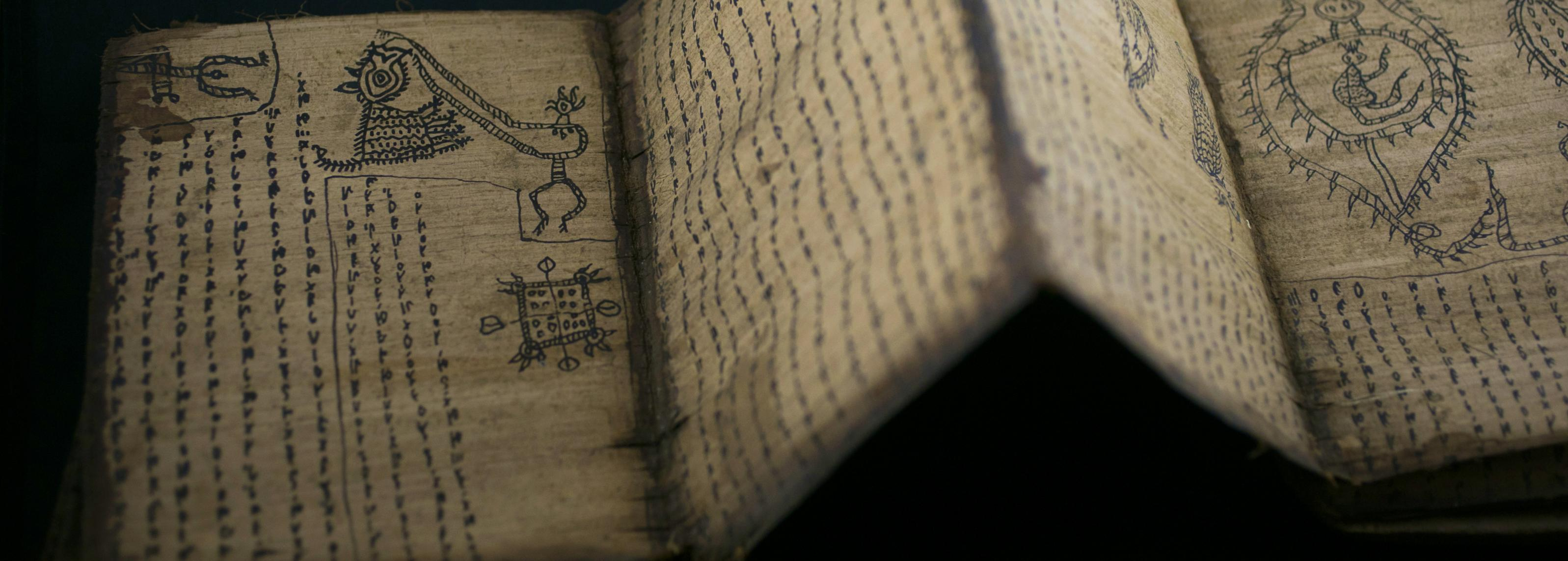 An open book with hand-drawn symbols and illustrations. The pages are folded like an accordion.