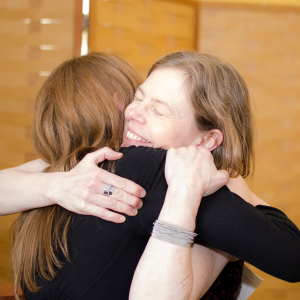 Smiling woman hugging another woman