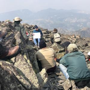A group of students sit on a mountainside.